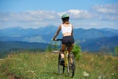 Bicicleta feliz joven del montar a caballo de la mujer en las montañas en el día de verano imagenes de archivo