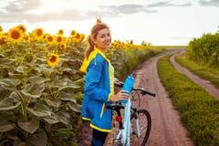 Bicicleta feliz nova da equitação do ciclista da mulher no campo do girassol Atividade do esporte do ver?o Estilo de vida saud?ve imagem de stock