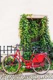 Bicicleta femenina roja que se inclina contra una cerca de carril Imágenes de archivo libres de regalías