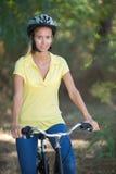 Bicicleta hermosa del montar a caballo de la muchacha en bosque Fotografía de archivo libre de regalías
