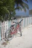 A bicicleta inclinou-se acima de encontro a uma cerca de piquete colorida Foto de Stock Royalty Free
