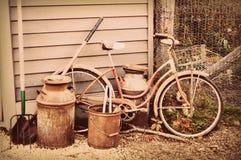 Bicicleta, jarro de leche y herramientas antiguos Foto de archivo
