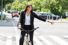 Bicicleta joven de Showing Turn On de la empresaria foto de archivo libre de regalías
