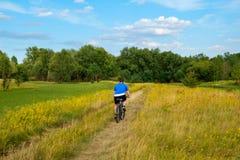 Bicicleta joven del montar a caballo del ciclista a través del prado verde contra el cielo hermoso Imagen de archivo