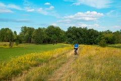 Bicicleta joven del montar a caballo del ciclista a través del prado verde contra el cielo hermoso Fotos de archivo libres de regalías