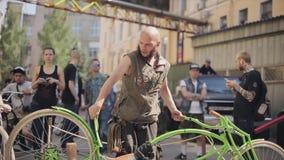Bicicleta larga del hombre del verde barbudo del soporte conforme a otra diferente en la calle exposición Día asoleado metrajes