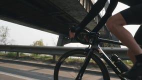 Bicicleta masculina da equitação do ciclista e engrenagens em mudança Brilho e ponte de Sun no fundo Perto siga acima o tiro Conc vídeos de arquivo