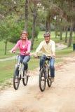 Bicicleta mayor del montar a caballo de los pares en parque Fotografía de archivo libre de regalías