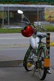 Bicicleta motorizada velha e capacete vermelho Imagem de Stock
