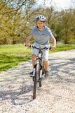 Bicicleta nova da equitação do menino ao longo da trilha do país Fotos de Stock Royalty Free