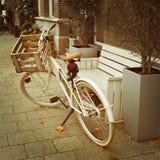 Bicicleta parqueada cerca de banco en la calle Fotografía de archivo