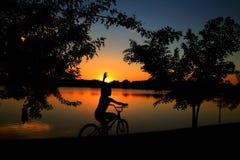 Bicicleta pedaling da criança no crepúsculo da lagoa fotografia de stock