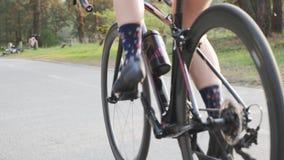 Bicicleta pedaling de ciclo de la muchacha del triathlete femenino en parque Ci?rrese encima de pedales en el movimiento Concepto metrajes