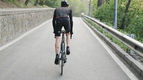 Bicicleta pedaling enfocada apta del ciclista fuera de la silla de montar ascendente Piernas fuertes con pedaling de los músculos almacen de metraje de vídeo