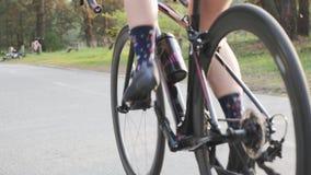Bicicleta pedalling de ciclo de la muchacha del triathlete femenino en parque Ci?rrese encima de pedales en el movimiento Concept almacen de metraje de vídeo