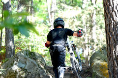 Bicicleta praticando do moutain do homem novo na floresta Fotos de Stock Royalty Free
