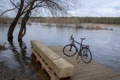 Bicicleta preta em uma ponte de madeira perto do rio fotos de stock