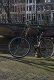 Bicicleta preta usual perto do canal no centro de Amsterdão imagem de stock