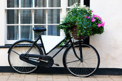 Bicicleta publicitaria vieja con la cesta de flores Fotografía de archivo libre de regalías