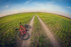 Bicicleta que encontra-se em uma estrada de terra no campo, distorção do fisheye imagens de stock royalty free