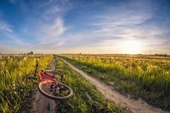 Bicicleta que encontra-se em uma estrada de terra em um campo no por do sol fotografia de stock