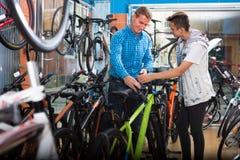 Bicicleta que hace compras del adolescente del hombre y del muchacho nueva en tienda del deporte Imágenes de archivo libres de regalías