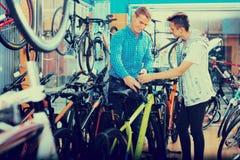 Bicicleta que hace compras del adolescente del hombre y del muchacho nueva en tienda del deporte Fotos de archivo