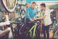 Bicicleta que hace compras del adolescente del hombre y del muchacho nueva en tienda del deporte Imagenes de archivo