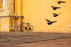 Bicicleta que inclina-se contra a parede amarela imagens de stock