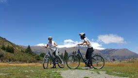 Bicicleta que monta de los pares románticos en paisaje hermoso imagen de archivo