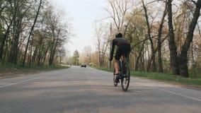 Bicicleta que monta del triathlete confiado fuerte en el parque Detr?s siga el tiro Concepto del Triathlon almacen de metraje de vídeo