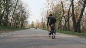 Bicicleta que monta del triathlete confiado fuerte en el parque Detr?s siga el tiro Concepto del Triathlon C?mara lenta metrajes