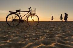 Bicicleta que se coloca en la playa durante puesta del sol Fotos de archivo libres de regalías