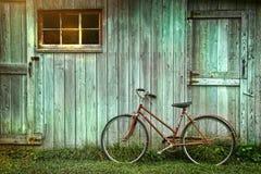 Bicicleta que se inclina contra granero sucio Foto de archivo libre de regalías