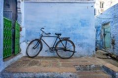 Bicicleta que se inclina en la pared azul foto de archivo libre de regalías