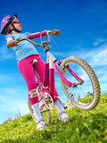 Bicicleta que viaja de la mujer en hierba verde en parque del verano Foto de archivo