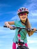 Bicicleta que viaja de la mujer en hierba verde en parque del verano Foto de archivo libre de regalías