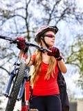 Bicicleta que viaja de la mujer en hierba verde en parque del verano Fotografía de archivo