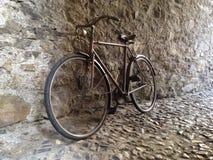 Bicicleta retra del vintage que se inclina contra una pared de piedra Imagenes de archivo