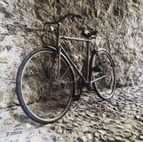 Bicicleta retra del vintage que se inclina contra una pared de piedra Fotos de archivo libres de regalías
