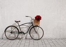 Bicicleta retro com cesta e flores na frente da parede velha, fundo Fotos de Stock