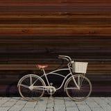 Bicicleta retro com a cesta na frente da parede de madeira colorida, fundo Fotos de Stock Royalty Free