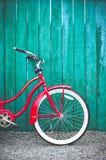 Bicicleta retro vermelha do estilo do ` s das mulheres que inclina-se contra uma cerca de madeira brilhante do verde azul imagens de stock royalty free