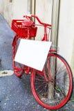 Bicicleta roja con el cartel vacío blanco Imágenes de archivo libres de regalías