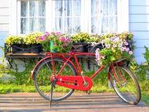Bicicleta roja delante de la ventana blanca retra Imágenes de archivo libres de regalías