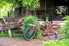 Bicicleta roja en el jardín Fotos de archivo