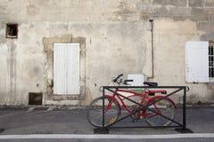 Bicicleta roja moderna delante de una casa vieja Imagen de archivo