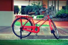 Bicicleta roja que parquea con la cesta para el modelo Fotografía de archivo