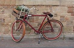 Bicicleta roja que se coloca delante de la pared Fotos de archivo