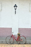 Bicicleta roja vieja en la calle antigua Imagen de archivo libre de regalías